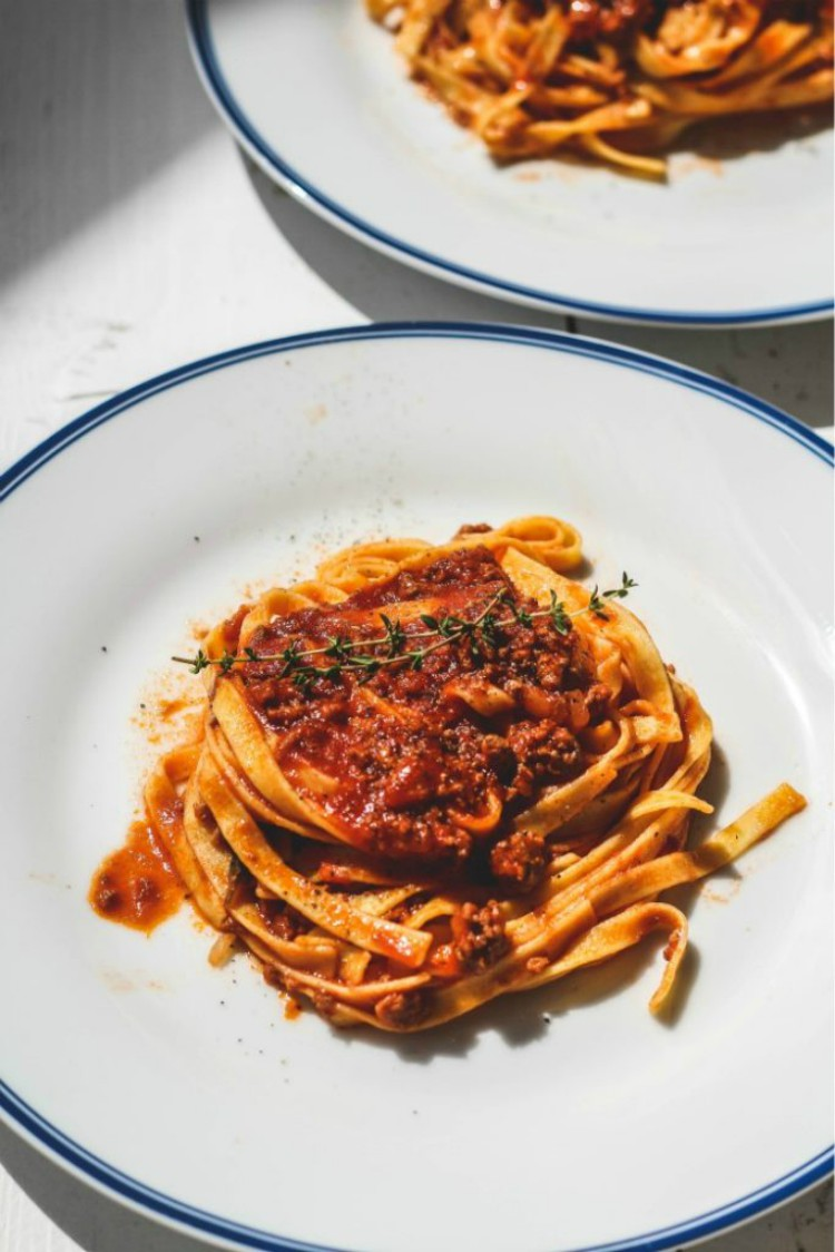overhead image of pasta with meat sauce on white plates
