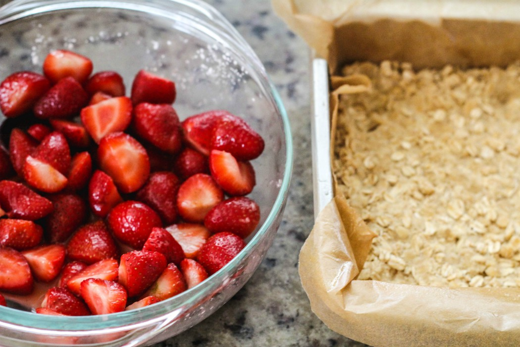overhead image of strawberries in bowl and an oat crust