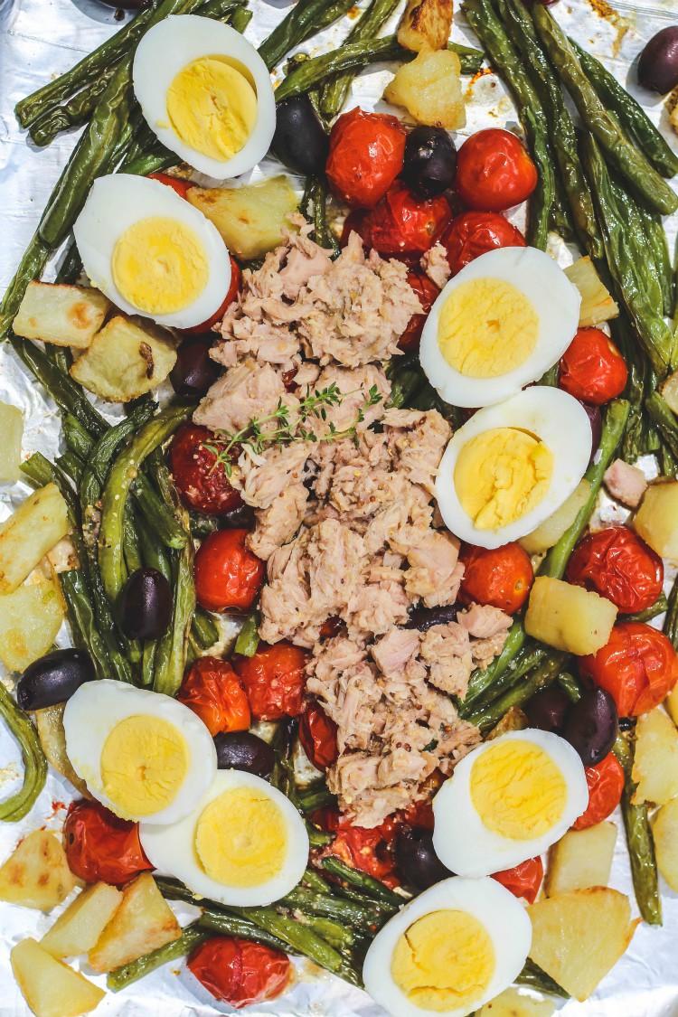 overhead image of warm tuna nicoise salad on a sheet pan