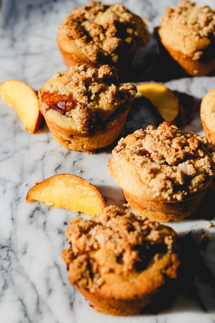 overhead image of peach streusel muffins on marble top