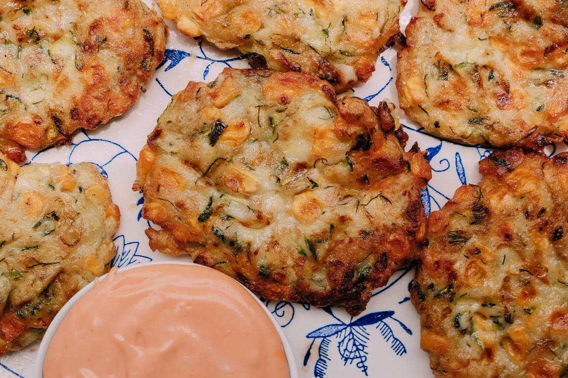 overhead image of zucchini and corn fritter on a serving plate