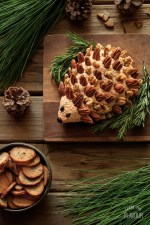 woodland hedgehog cheese ball with rosemary sprigs, frozen cranberries, and a bowl of crackers