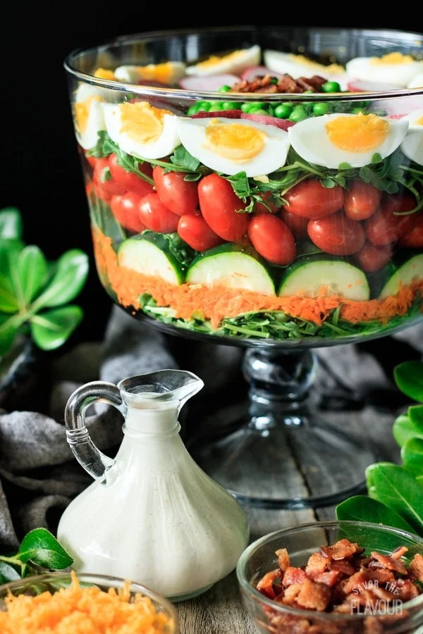 homemade salad dressing with layered salad in a glass bowl