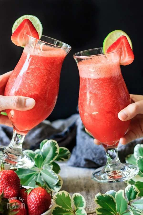 two people doing a toast with strawberry daiquiri drinks