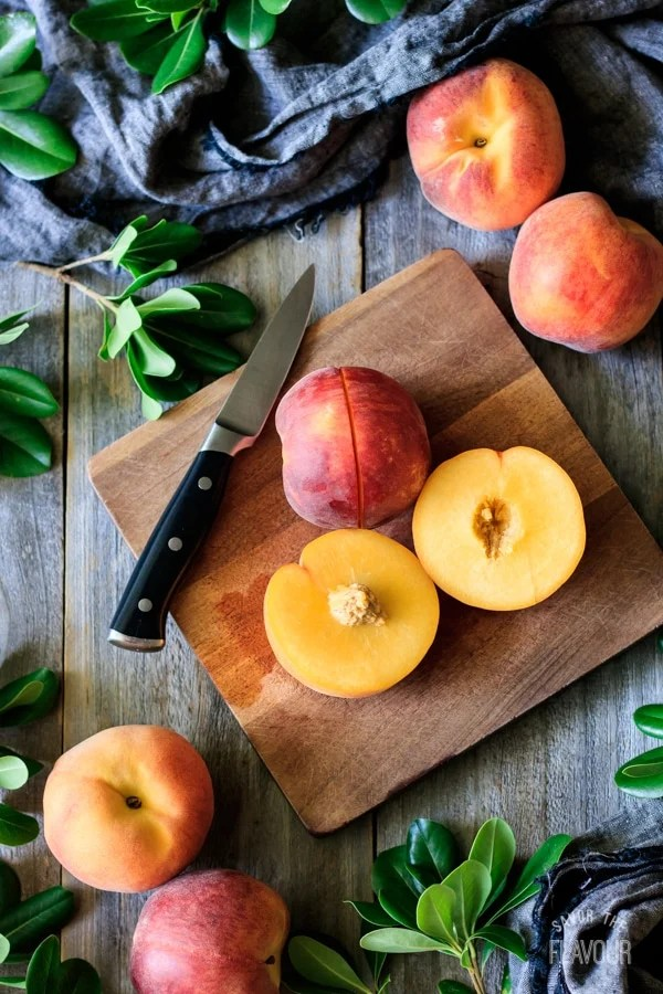 fresh peaches on a cutting board with a knife