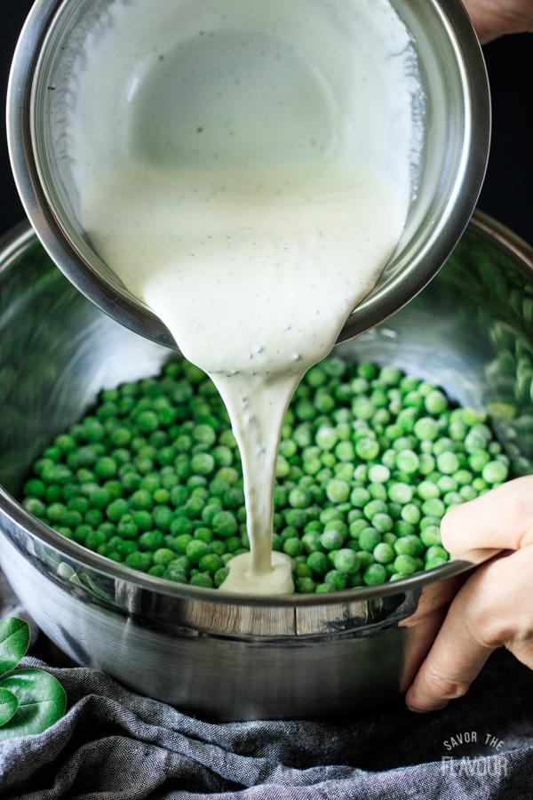 pouring dressing onto peas for pea salad