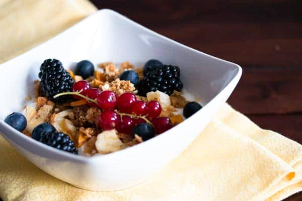 white bowl filled with granola and fresh berries