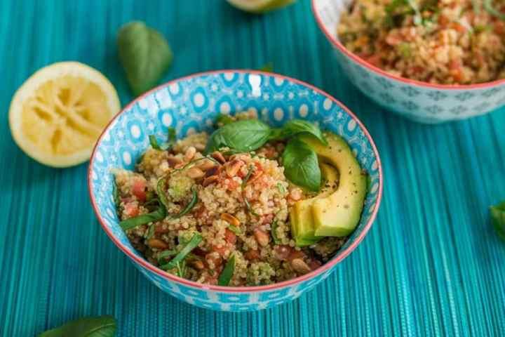 bowl of quinoa salad on a blue backdrop
