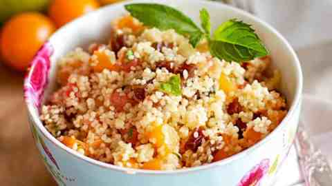 floral bowl with couscous salad in front of colourful tomatoes
