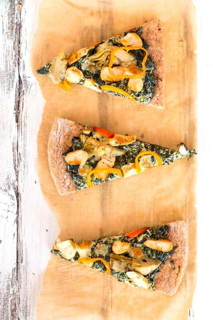 three slices of spinach artichoke pizza on a piece of baking parchment