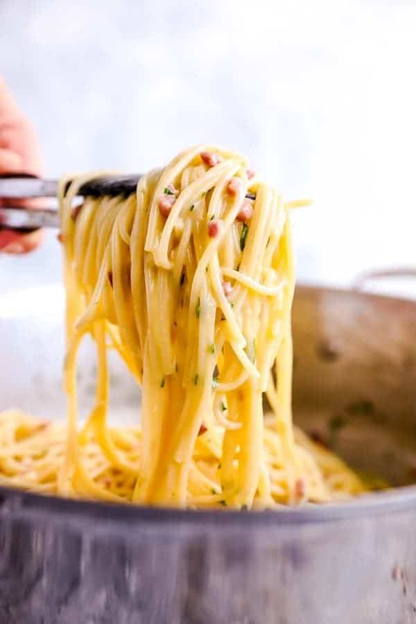 scooping pasta carbonara out of a pot with kitchen tongs