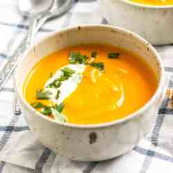 frontal view of white bowl filled with carrot soup