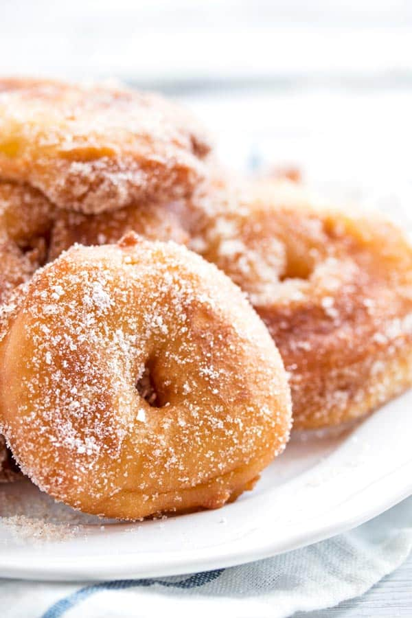 a pile of apple fritters on a white plate