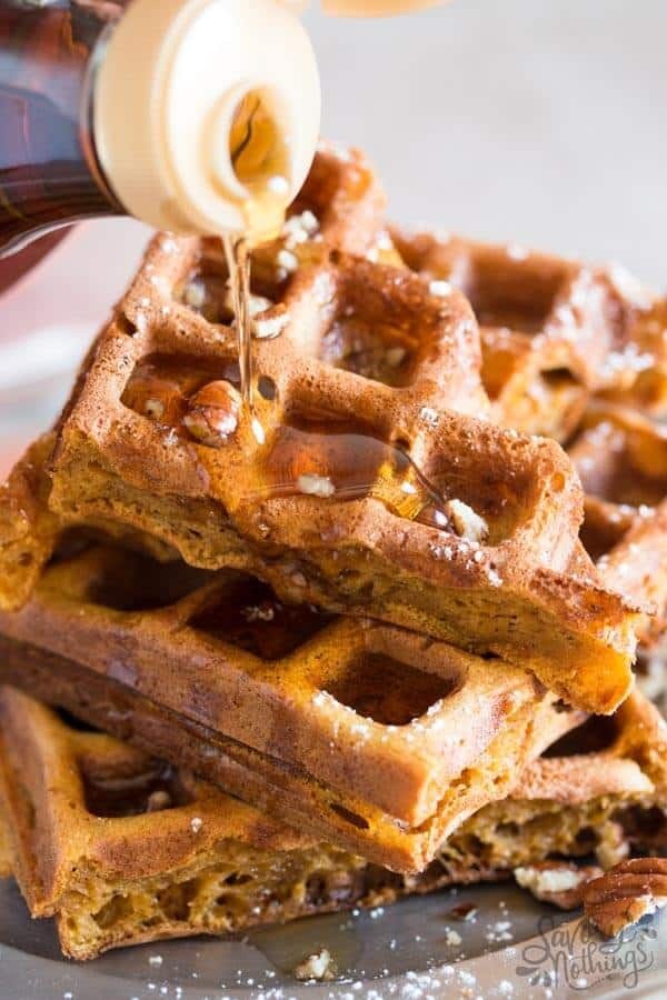 stack of pumpkin waffles, drizzling with maple syrup