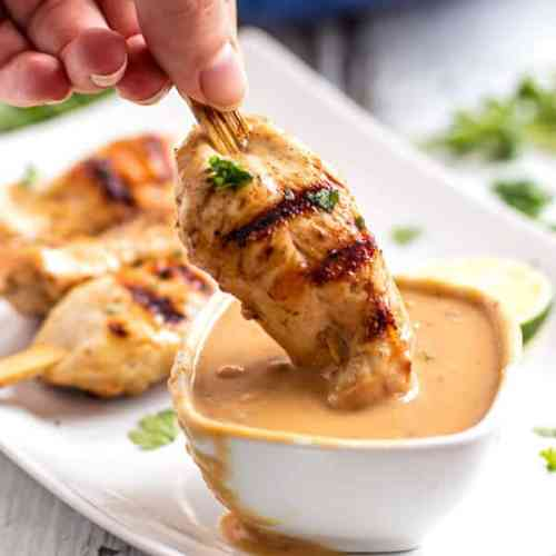 female hand dipping grilled chicken in peanut sauce