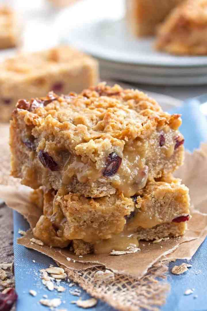 stack of Cranberry White Chocolate Oatmeal Bars on a blue napkin