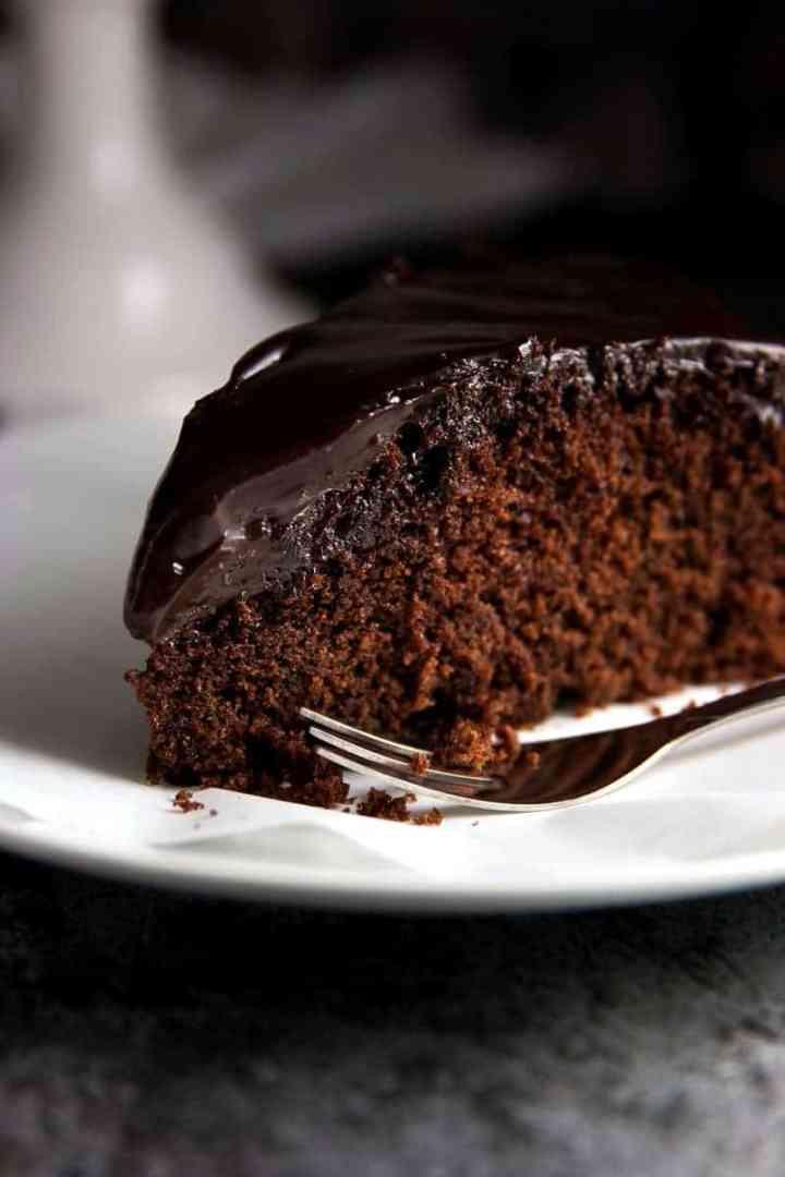 close up photo of chocolate honey cake on white plate