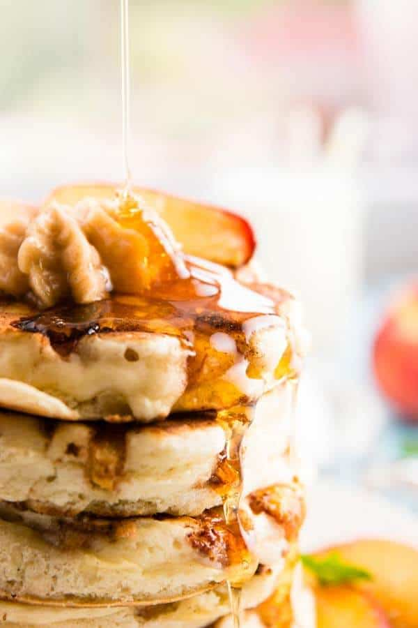 drizzling maple syrup over pancakes