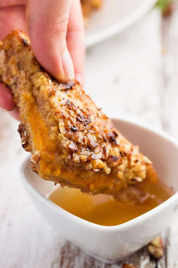 dipping pumpkin French toast in maple syrup