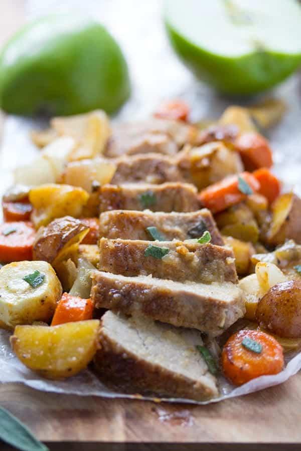 sliced pork tenderloin with vegetables on wooden board