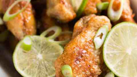 white enamel dish filled with crispy chicken wings, lime slices and chopped green onion on pink napkin