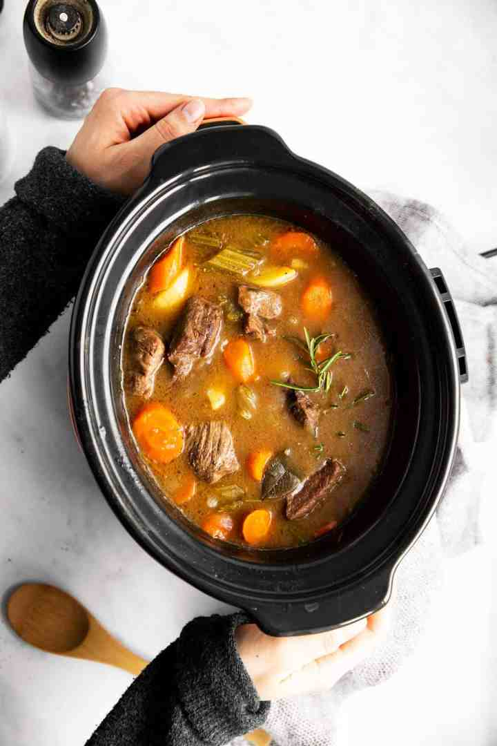 woman holding a slow cooker filled with Irish beef stew