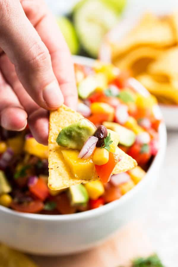 female hand holding tortilla chip with mango avocado black bean salsa