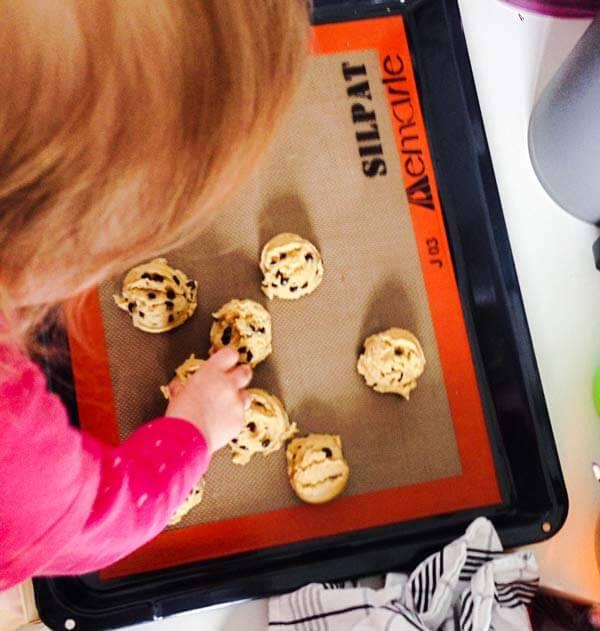 Kid arranging chocolate chip cookie dough.