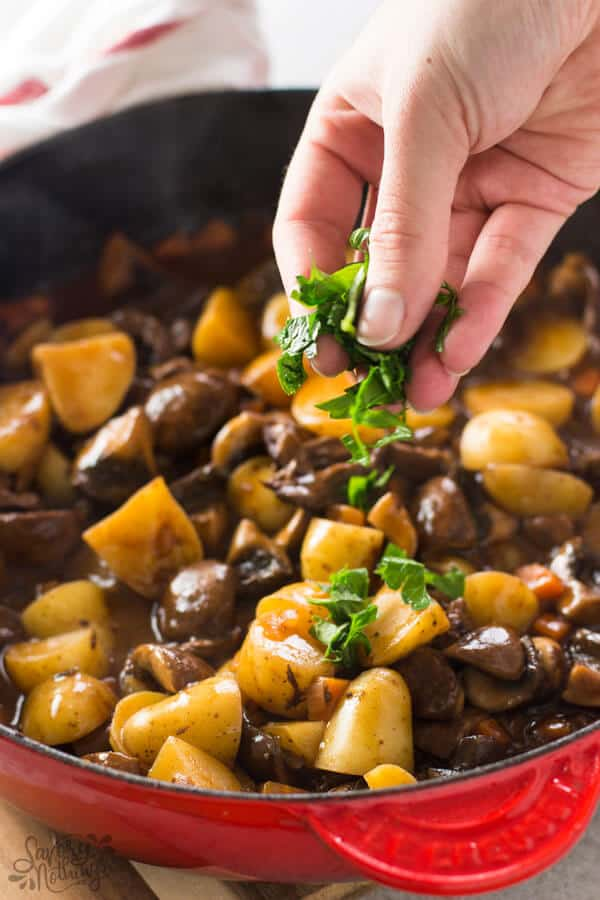 Sprinkling fresh parsley on beef tips and gravy skillet.