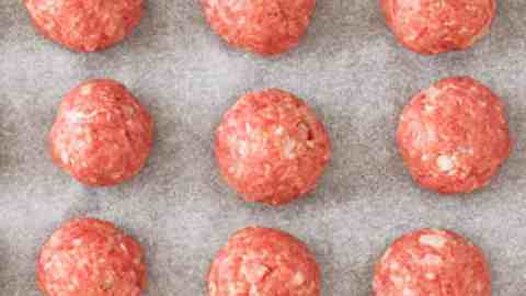 nine raw meatballs on parchment