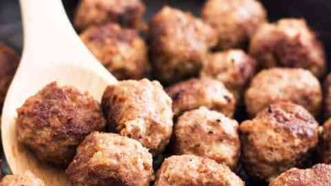 close up photo of pan-fried meatballs in black cast iron skillet with wooden spoon