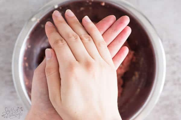 female hands rolling a meatball