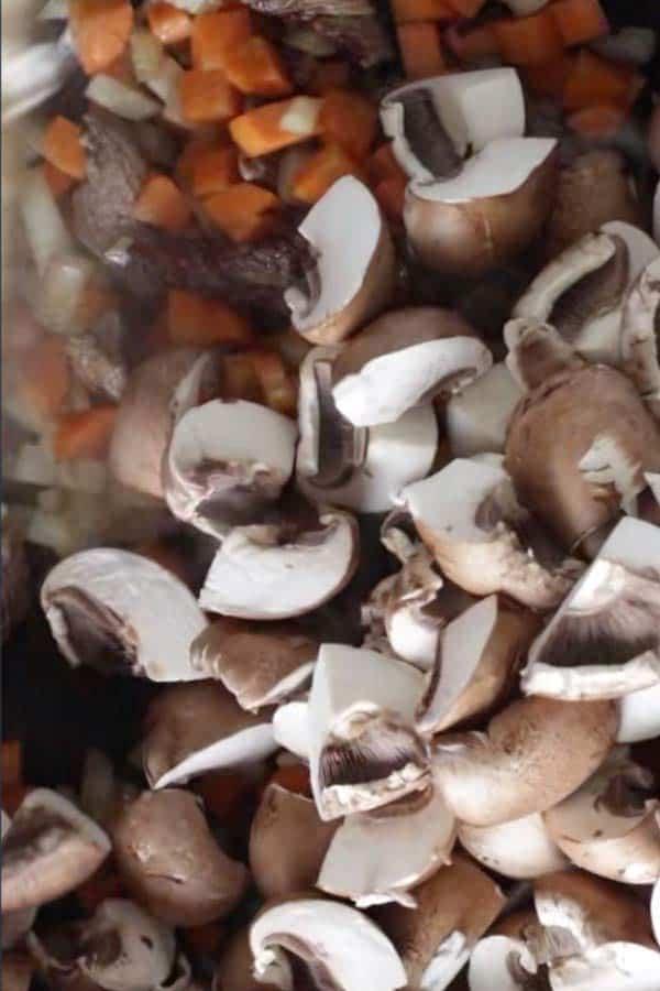 raw sliced mushrooms in a skillet