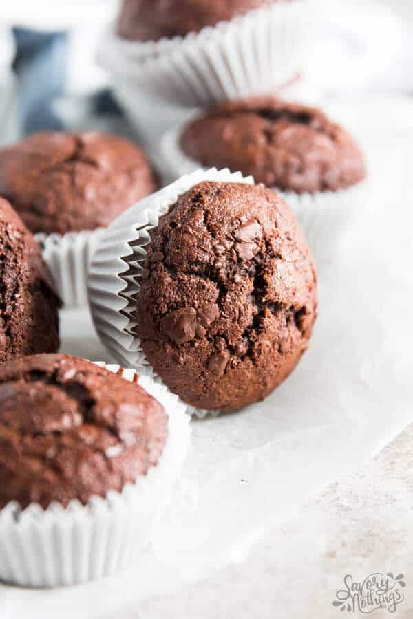 pile of chocolate banana muffins on parchment paper