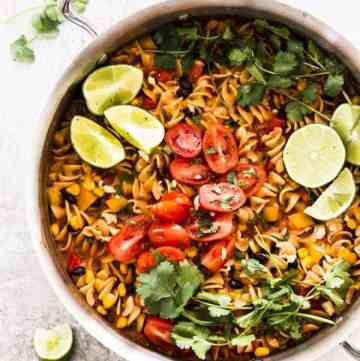 overhead photo of skillet with enchilada pasta, topped with cilantro, limes and tomatoes