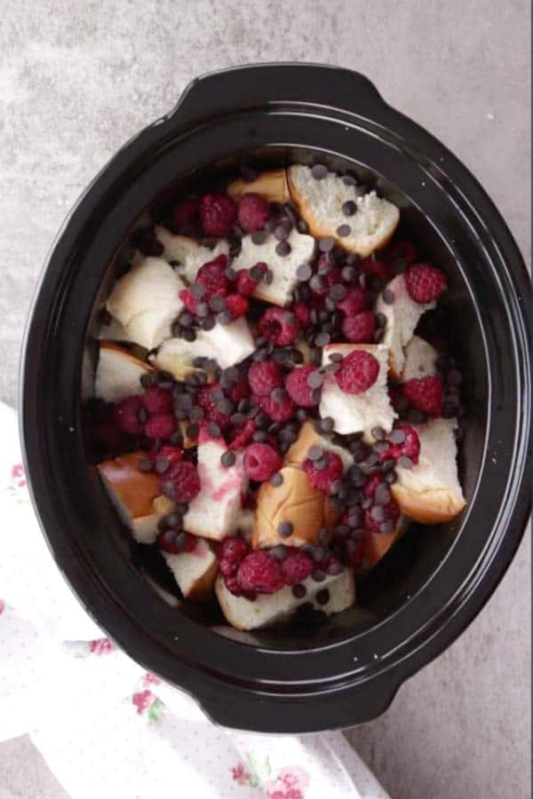 black crock from a slow cooker filled with cubed challah bread, raspberries and chocolate chips