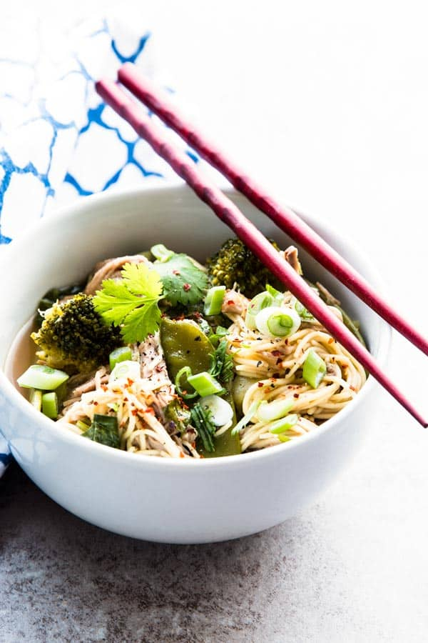 asian pork and noodles in white bowl with red chopsticks