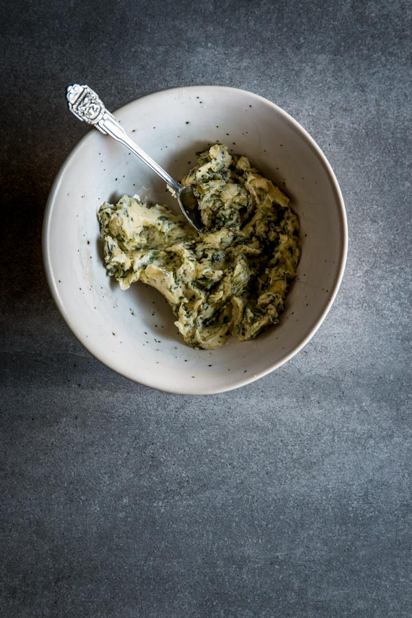 Garlic herb compound butter for baked whole fish in white bowl