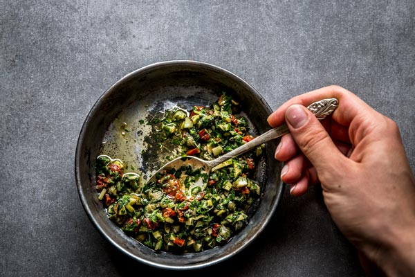 Briny caper and sun dried tomato salsa to go on baked whole fish. Beautiful still life food photography and styling.