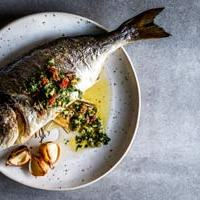 Whole Baked Fish with Lemon Herb Garlic Butter and a fresh herb salsa on a white plate.