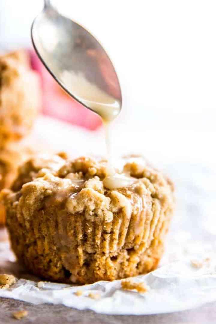 cinnamon glaze running from spoon on apple muffin