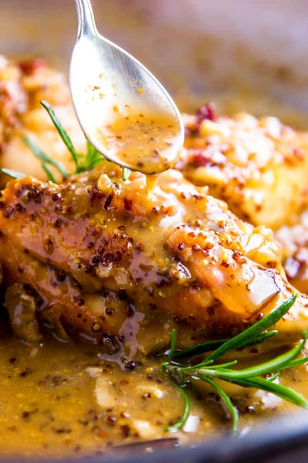 Drizzling sauce on Honey Mustard Chicken with a spoon