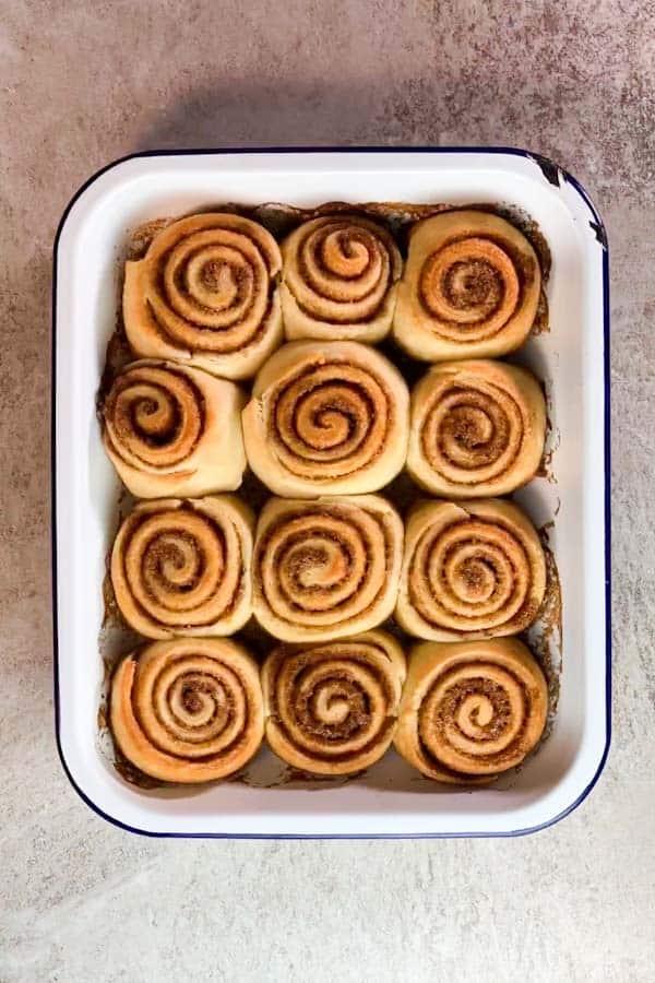 cinnamon rolls in a white enamel pan after baking