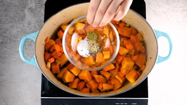 Adding spices to pumpkin soup.