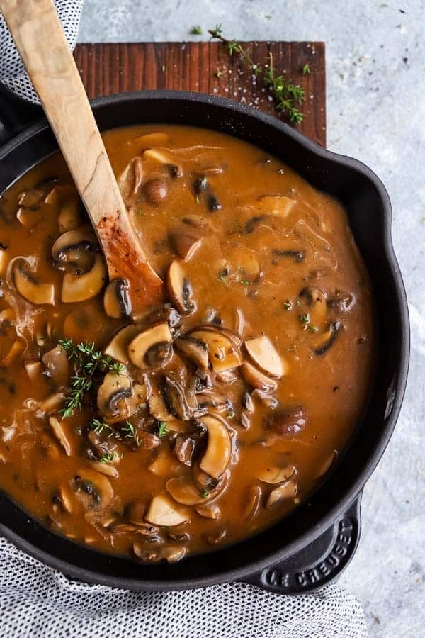 cast iron skillet with mushroom gravy on a wooden board