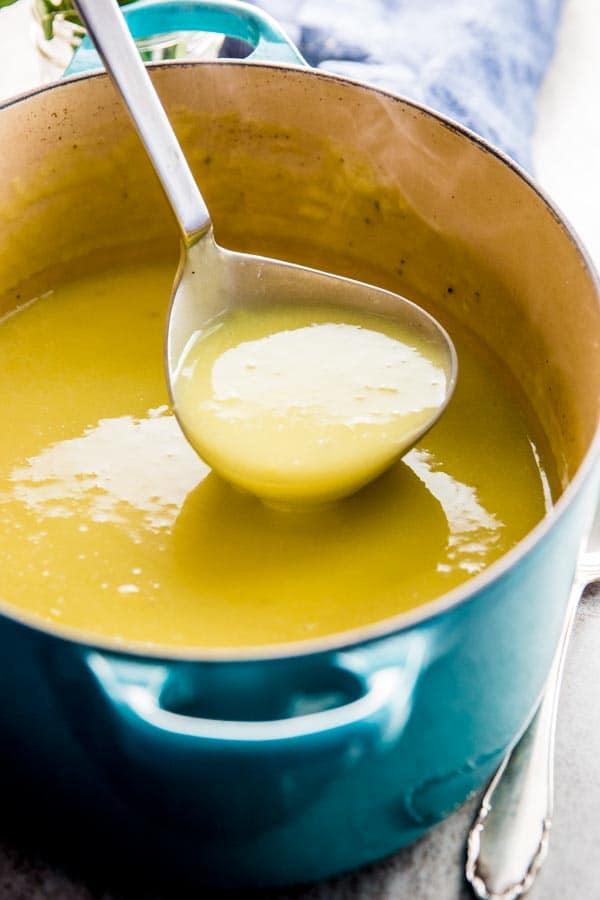 ladling potato leek soup out of blue Dutch oven