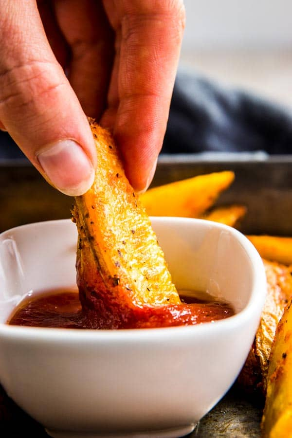 Dipping baked potato wedges in ketchup