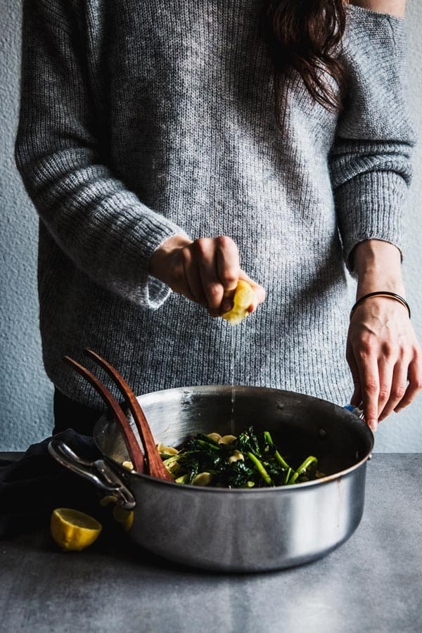 Woman squeezing a lemon over broccoli rabe pasta.