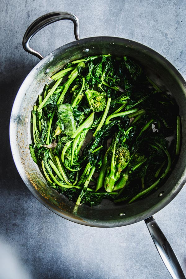 Wilted broccoli rabe in a skillet.