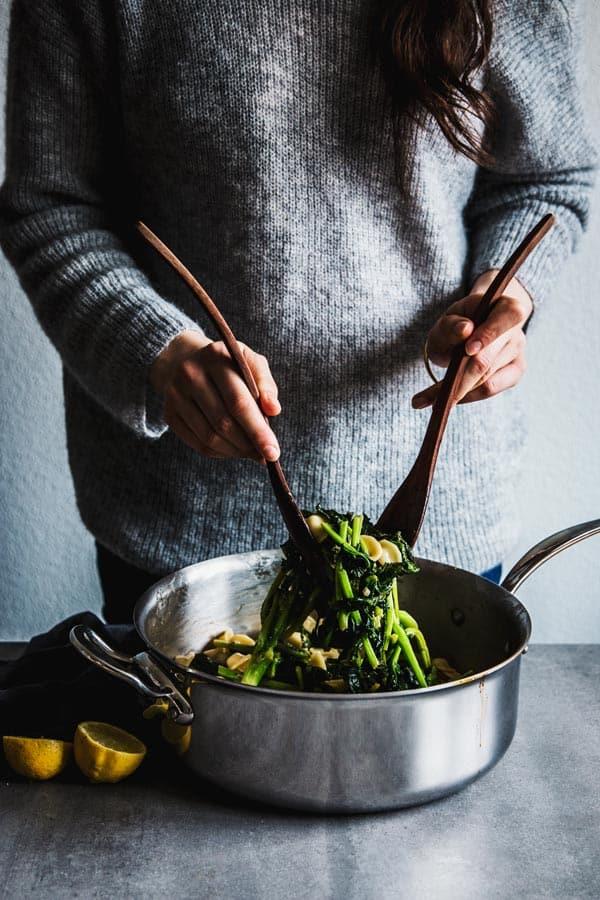Woman tossing broccoli rabe pasta.